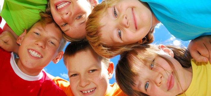 Kids in a circle smiling.